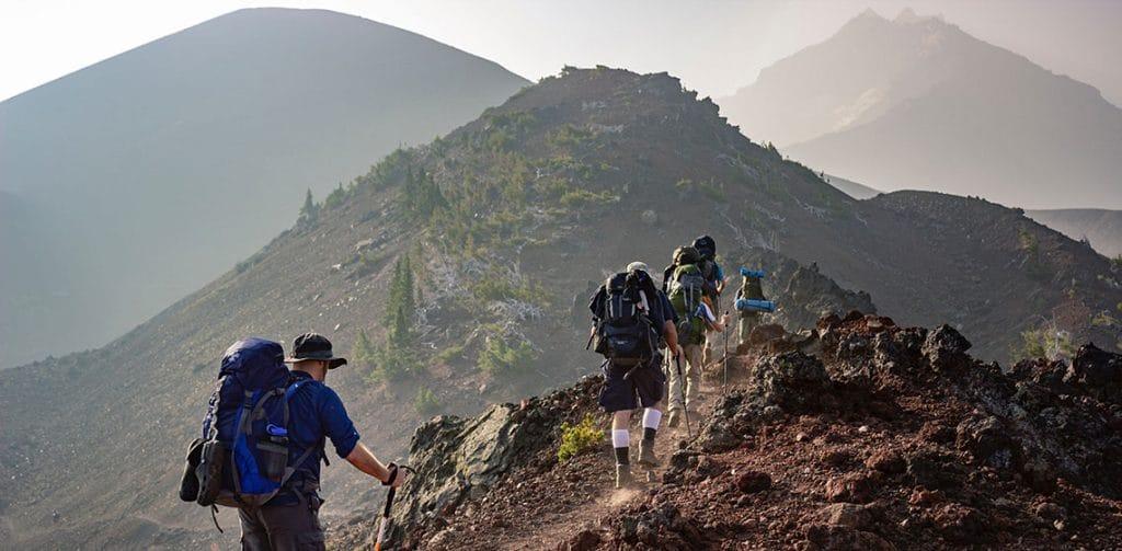 Ruta de montaña con amigos respirando aire puro. razones para comprar moda sostenible